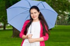 拿着伞的微笑的少妇 库存图片