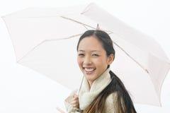 拿着伞的快乐的亚裔妇女画象  库存图片