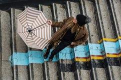 拿着伞的时髦女孩,站立在台阶 库存照片