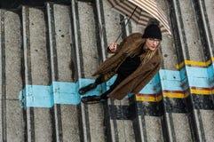 拿着伞的时髦女孩,站立在台阶 库存图片