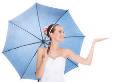 拿着伞的白色礼服的俏丽的新娘妇女 免版税库存照片
