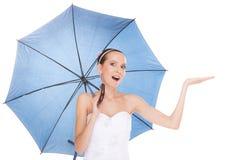 拿着伞的白色礼服的俏丽的新娘妇女 免版税库存图片