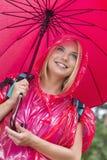 拿着伞的红色雨衣的微笑的女性远足者 免版税库存照片