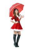 拿着伞的美丽的圣诞老人帮手女孩微笑和看照相机 库存照片