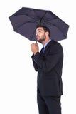 拿着伞的衣服的女实业家,当查寻时 免版税库存照片