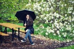拿着伞,庭院的女孩 图库摄影