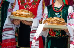 拿着传统美丽的大面包的种族保加利亚衣裳的女孩 免版税库存图片