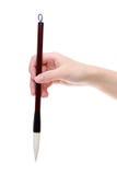 拿着传统笔的手 免版税库存照片
