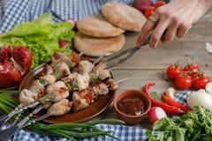 拿着伪造的叉子的手趋向对水多的kebabs 在开火烹调的肉 在木背景的静物画 特写镜头 库存图片