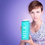 拿着低脂牛奶纸盒的严肃的妇女 免版税库存图片