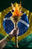 拿着体育火炬巴西旗子的巴西运动员 免版税图库摄影