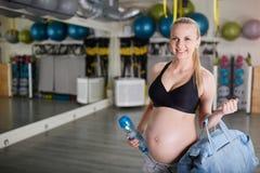 拿着体育袋子和bidon的健身房的愉快的孕妇 免版税库存图片