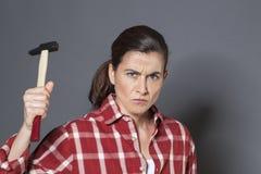 拿着侵略或自卫的不快乐的30s妇女锤子 库存图片