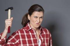 拿着侵略或自卫的恼怒的30s妇女锤子 免版税库存图片