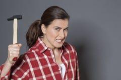 拿着侵略或自卫的愤怒的30s妇女锤子 免版税库存照片