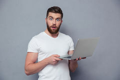 拿着便携式计算机的惊奇人画象  免版税库存照片