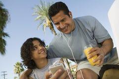 拿着便携式音乐播放父亲的男孩(13-15)听与耳机和拿着杯汁液。 免版税库存照片