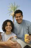 拿着便携式音乐播放父亲的男孩(13-15)听与耳机每举行的杯汁液正面图画象。 免版税库存图片