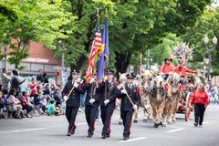 拿着俄勒冈和美国的旗子的穿制服的男性 免版税库存图片
