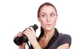 拿着俏丽的妇女的双筒望远镜 库存照片