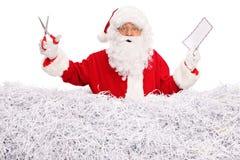 拿着信封和剪刀的圣诞老人 库存图片