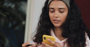 拿着信用卡和使用在床上的可爱的女孩智能手机 在网上购物与手机的愉快的年轻女人和 股票录像