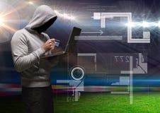 拿着信用卡和使用在草地前面的黑客一台膝上型计算机 库存图片