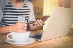 拿着信用卡和使用巧妙的电话的人的手 免版税库存图片