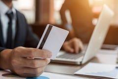 拿着信用卡和使用手提电脑的商人 免版税图库摄影