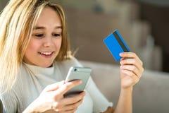 拿着信用卡和使用手机的女孩 免版税库存照片