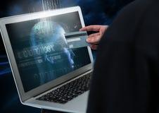 拿着信用卡和使用有数字式面孔的黑客一台膝上型计算机在屏幕上 库存照片
