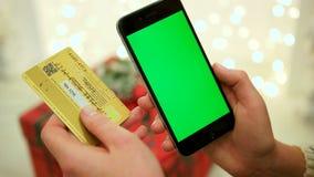 拿着信用卡和使用流动巧妙的电话的手在网上购物 特写镜头 关闭 跟踪行动 迷离 影视素材