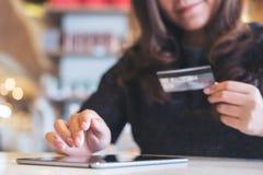 拿着信用卡和使用片剂个人计算机的一名兴高采烈的面孔亚裔妇女在餐馆 免版税库存图片