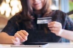 拿着信用卡和使用片剂个人计算机的一名兴高采烈的面孔亚裔妇女在餐馆 库存照片