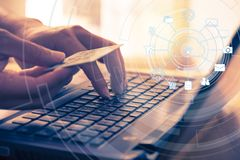 拿着信用卡和使用膝上型计算机的手为网上购物和付款 库存照片