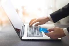 拿着信用卡和使用膝上型计算机, onlin的商人的手 免版税库存图片