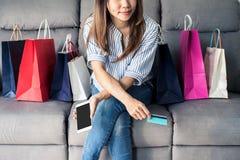 拿着信用卡和巧妙的电话的愉快的亚裔妇女 库存图片