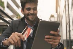拿着信用卡和数字式片剂的商人 免版税库存照片