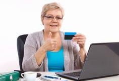 拿着信用卡和显示赞许的年长资深妇女,支付在互联网电费单或购物 免版税库存照片