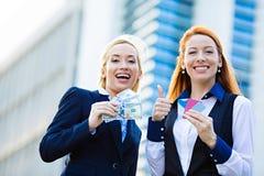 拿着信用卡和现金奖励的愉快的女商人 免版税库存照片