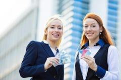 拿着信用卡和现金奖励的愉快的女商人 库存照片