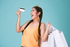 拿着信用卡和购物袋的快乐的年轻深色的妇女画象  免版税图库摄影