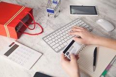拿着信用卡和键入在键盘的手 r 免版税库存图片