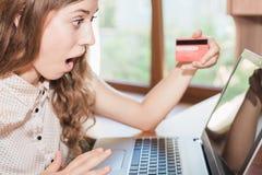 拿着信用卡和购物通过膝上型计算机的美丽的惊奇的妇女 免版税库存照片