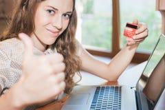 拿着信用卡和购物通过膝上型计算机的美丽的成功的妇女 免版税库存图片