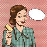 拿着信用卡在减速火箭的流行艺术样式的妇女传染媒介例证 购物与银行卡概念 免版税库存图片