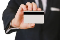 拿着信用卡的商人提出它对您 在bla的手 免版税图库摄影