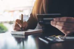 拿着信用卡的妇女,当写下在桌上时的笔记本 图库摄影