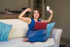 拿着信用卡的年轻美丽和愉快的妇女激动的在家客厅长沙发生活方式画象使用手提电脑 免版税库存图片