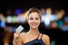 拿着信用卡的晚礼服的微笑的妇女 库存照片